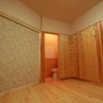 室内 after 左側がキッチンでロールスクリーンで仕切っている。右側の壁の金属は棚受け。